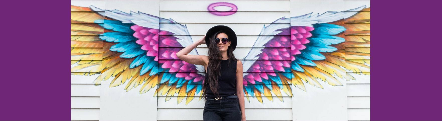 A woman standing in front of a pair of graffiti angel wings