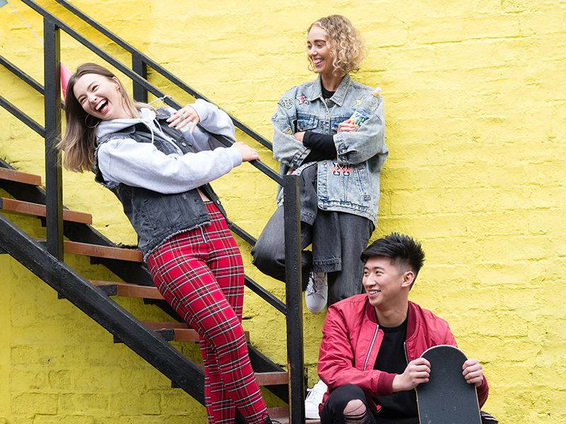 A group of three people laughing and hanging out on a set of stairs
