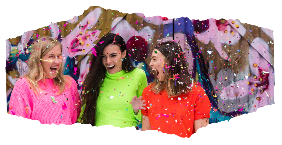 Three woman under confetti before a colourful wall