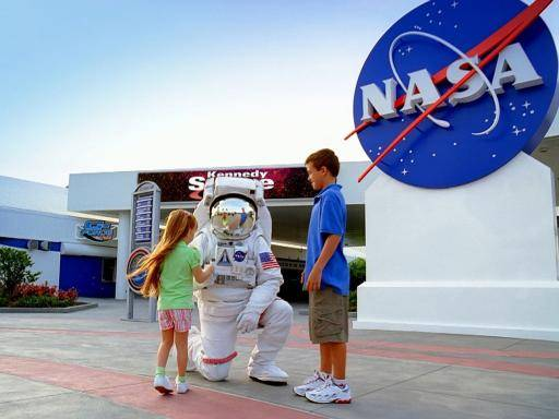 astronaut kneeling down to two children outside space centre